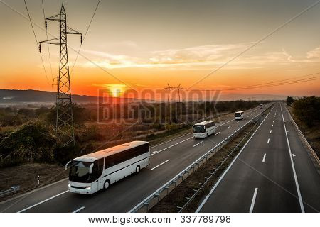 Caravan Or Convoy Of Four Buses In Line Traveling On A Country Highway Under Amazing Orange Sunset S