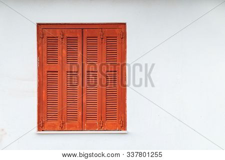 Greek Style Windows - Wooden Vintage Window With Brown Shutters On A White Wall. Closed House Window