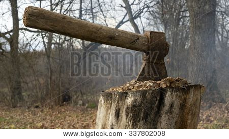 An Old Ax Sticking Out In A Deck Outdoors. Close-up Of An Ax On A Background Of Wooden Decks