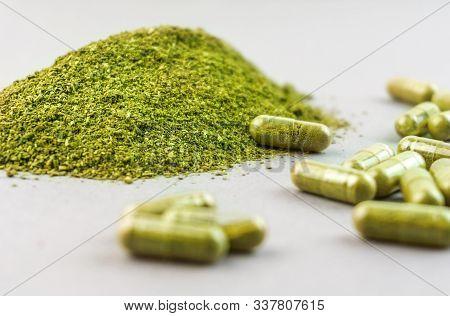 Coarse Grind Mitragynina Speciosa Or Kratom Powder And Kratom Pills On Grey Background