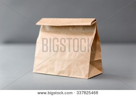 recycling, reuse and ecology concept - disposable brown takeaway food in paper bag with lunch on table