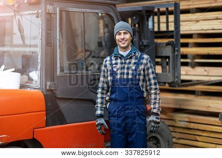 Young male worker standing next to the forklift in lumber yard