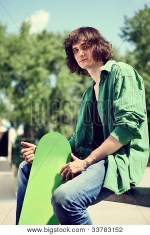 young skater sitting and posing with his skateboard, outdoor