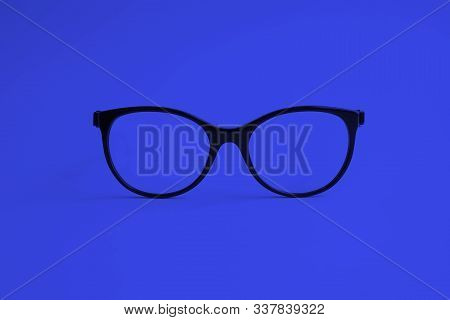Modern Fashionable Acetate Spectacles, Black Color, Laying On Deep Blue Background. Trendy Concept.