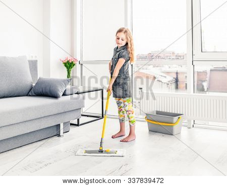 Little girl cleaning floor with mop