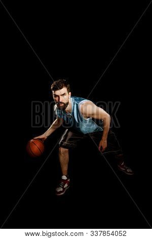 Skilled Sportsman Dribbling A Ball. Young And Muscular Basketball Player
