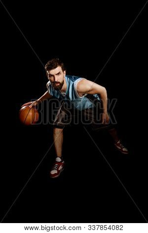 Player Dribbling A Basketball. Portrait Of Deft And Strong Sportsman