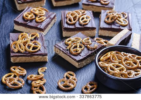 Close-up Of No-bake Chocolate Peanut Butter Bars Topped With Pretzel Crackers On A Slate Tray On A W
