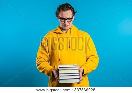 European Student On Blue Background Is Dissatisfied With Amount Of Homework And Books. Man Confused,