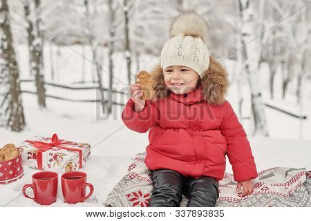 Happy Child Girl On Winter Walk Outdoors Drinking Tea. Smiling Baby Little Child Playing In Winter C
