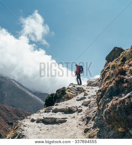 Hiker Man Silhouette On Clouds Background Standing On Path Going Over The Imja Khola Valley And Enjo