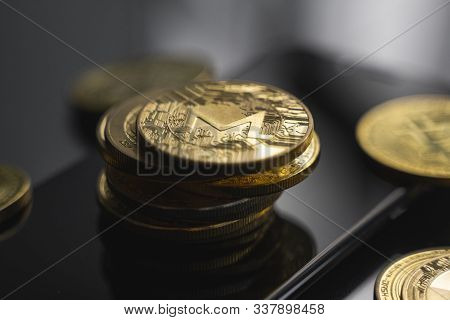 Stack Of Golden Monero Bitcoin Coin On A Smartphone With A Lot Of Bitcoins Coins On A Table. Virtual