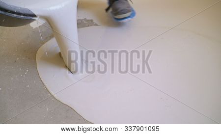 Workers Flood The Floor. Liquid Flooring. Leveling The Floor With A Liquid Composition. Industrial W
