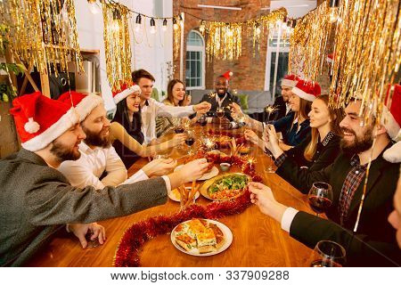 Happy Co-workers Celebrating While Company New Year And Christmas Party. Young Caucasian People In C