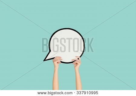 Hands Holding The Sign Of Comment On Blue Studio Background. Negative Space For Text Or Image, Adver