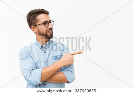 Positive Male Customer Presenting New Product, Pointing Finger At Copy Space. Handsome Young Man In
