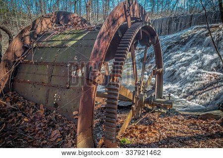 An Old Grist Mill Wheel Left Behind Decaying And Stuck Halfway In The Ground Rusting With The Waterf