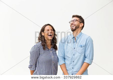 Excited Carefree Couple Laughing And Having Fun. Young Woman In Casual And Man In Glasses In Glasses