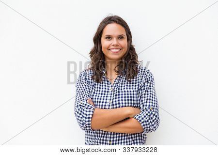 Happy Joyful Student Girl With Arms Folded Looking At Camera And Smiling. Young Woman In Casual Chec