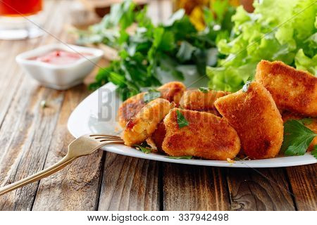 Fried Chicken Nuggets With Ketchup Sprinkled With Chopped Parsley.  Nuggets And Salad On A Old Woode