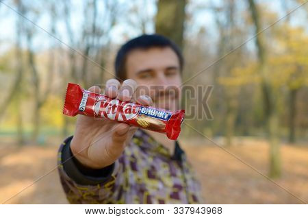 Kharkov, Ukraine - October 21, 2019: A Young Caucasian Bearded Man Shows Kit Kat Chocolate Bar In Re
