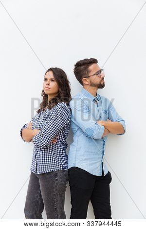 Sad Unhappy Couple Standing Back-to-back With Arms Crossed. Young Woman In Casual And Man In Glasses