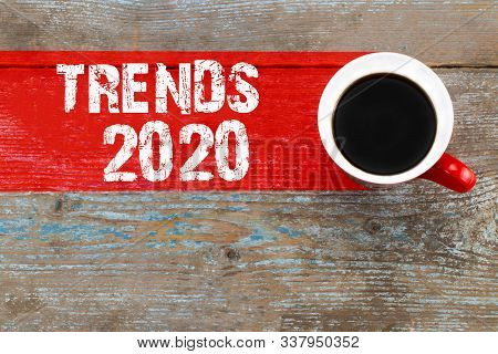Trends 2020 / Cup Of Coffee With Trends Inscription On Wooden Background.