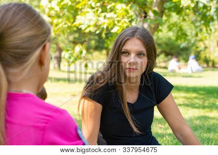 The Girl On A Picnic Listens Attentively To The Interlocutor
