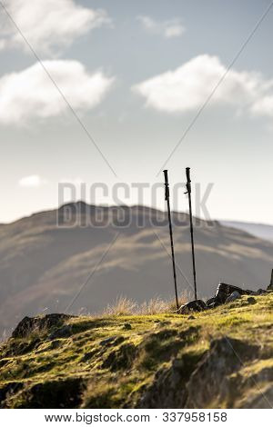 Walking Poles And Backpack On Ground Of Hills In Lake District Iwth Mountains And Bright Autumn Fall
