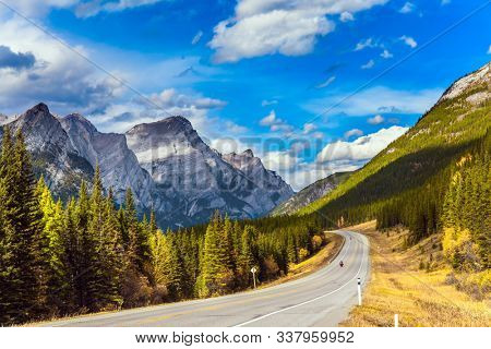 Rocky Mountain asphalt highway. Lush autumn in the Canadian Rockies. The mountain valley of provincial park. The concept of active, ecological and photo tourism