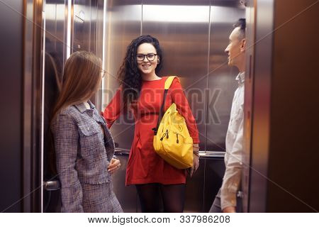 The Girls And The Guy Ride In The Elevator. Students In The Elevator Go To Study. People In The Elev
