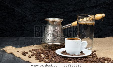 Hot Coffee In Turkish Cooper And Linen Table. Greek Coffee Pot, Glass Of Water And Coffee Beans Drop