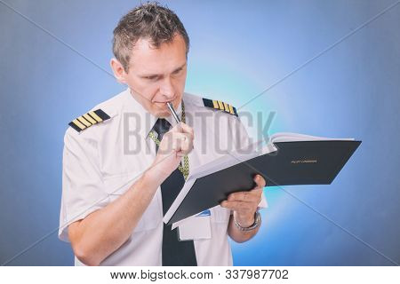 Airline pilot wearing shirt with epaulets and tie filling in filling in and checking papers logbook and checking papers and weather forecast