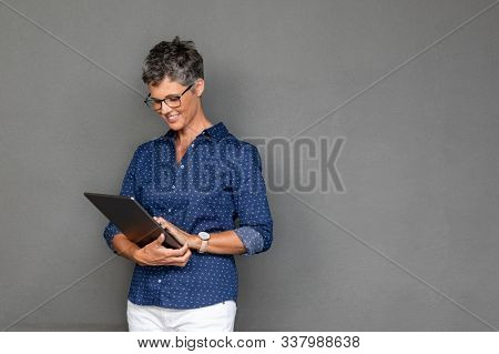 Smiling mature businesswoman wearing spectacles while using digital tablet against grey background with copy space. Beautiful middle aged woman checking email on laptop on gray wall.