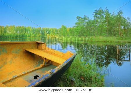 Boat With Holey On Lake Under Blue Sky