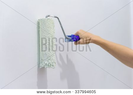 Painting Out A White Wall With A Paint Roller With White Paint. Close Up Female Hand Painting Wall W