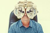 Caucasian man  checks eyesight in a clinician oculist. Man checks his vision on the machine checking patient vision at eye clinic or optics store. Male patient to check vision in ophthalmological clinic poster