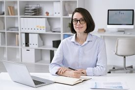Pretty young businesswoman in formalwear looking at you while sitting by desk in front of laptop and making notes