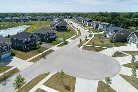 Aerial view of a housing community in a neighborhood with pond in a suburban location.
