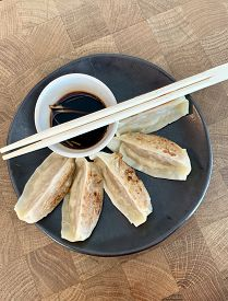 Gyoza And Chopsticks. Japanese Dumplings Consisting Of Wonton Wrappers Stuffed With Pork And Cabbage