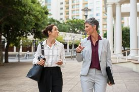Two business women in conversation walking on city street. Corporate colleagues discussing new project while going to work. Two mature formal women discussing business outdoor.