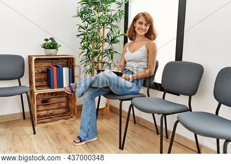 Young caucasian girl smiling happy writing on notebook sitting at waiting room.
