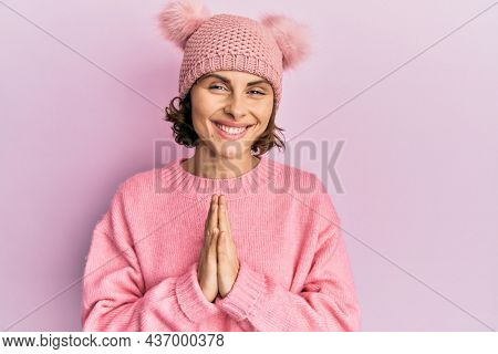 Young brunette woman wearing cute wool cap praying with hands together asking for forgiveness smiling confident.