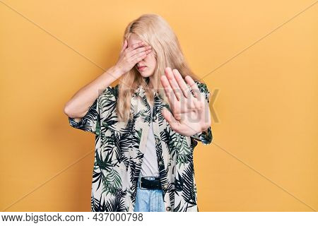 Beautiful caucasian woman with blond hair wearing tropical shirt covering eyes with hands and doing stop gesture with sad and fear expression. embarrassed and negative concept.