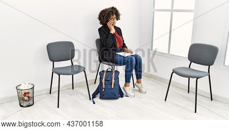 Young african american woman talking on the smartphone sitting on chair at waiting room