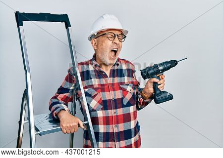 Handsome mature handyman holding screwdriver wearing hardhat by construction stairs angry and mad screaming frustrated and furious, shouting with anger. rage and aggressive concept.