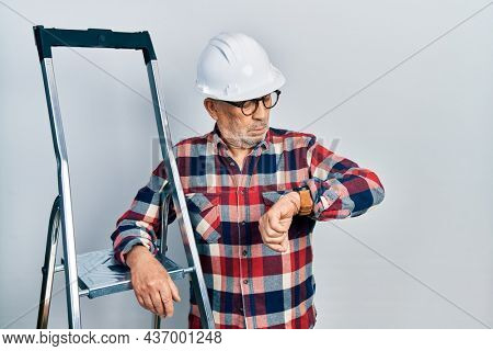 Handsome mature handyman close to construction stairs wearing hardhat checking the time on wrist watch, relaxed and confident