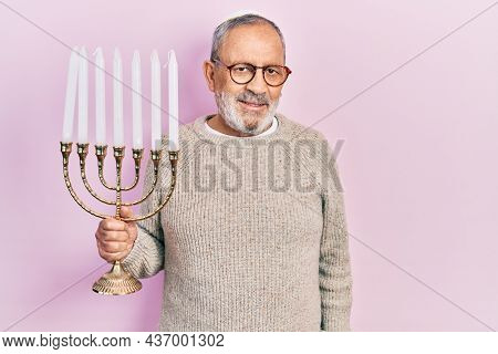 Handsome senior man with beard holding menorah hanukkah jewish candle looking positive and happy standing and smiling with a confident smile showing teeth