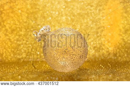 Christmas Background With A Christmas Tree Toy. Christmas Ball On A Yellow Background. Place For Chr