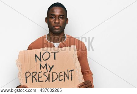 Young african american man holding not my president protest banner thinking attitude and sober expression looking self confident